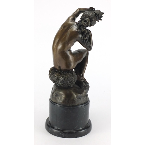 2033 - Patinated bronze figurine of a nude female holding a shell, raised on a circular black marble base, ...
