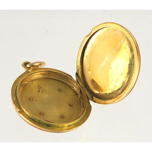 646 - Unmarked gold red guilloche enamelled locket with diamond snowflake decoration, 1.8cm in diameter, a...