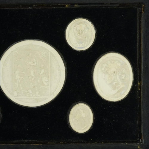 37 - Seven 19th century Grand Tour plaster plaques including six portraits, housed in a hanging display, ...