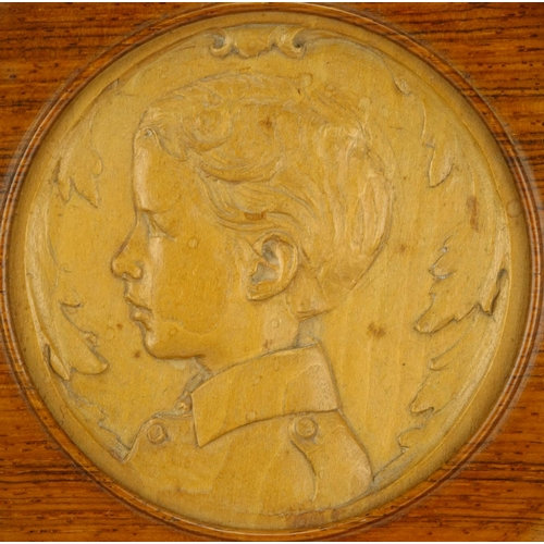 33 - Circular continental fruitwood carving of a young boy, housed in an oak framed, incised marks to the...