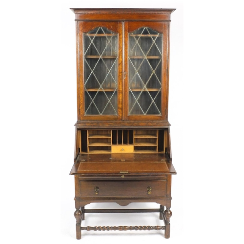 1 - Oak bureau bookcase fitted with a pair of leaded glass doors enclosing three shelves above a fall, w...