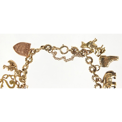 705 - 9ct gold charm bracelet with a selection of mostly gold charms including church, Dutch figure, pixie...