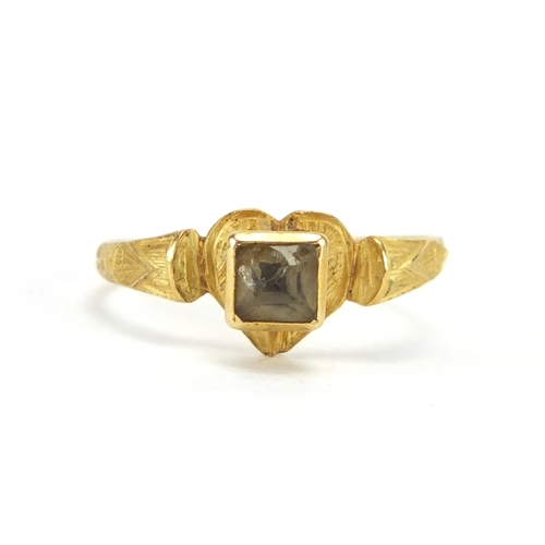 642 - Roman unmarked gold and glass love heart ring, the shoulders with engraved decoration, size J, appro...
