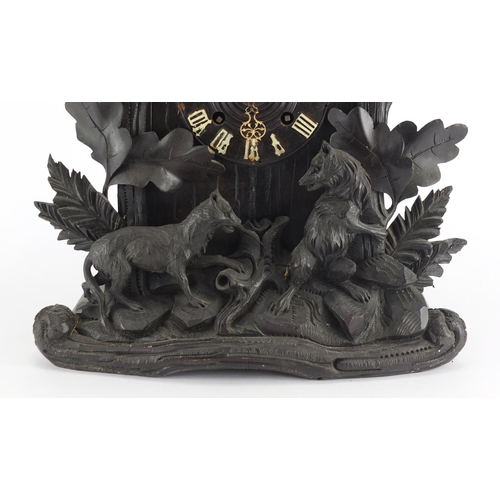 2045 - Black forest cuckoo clock carved with a bear, wolf and leaves, 50cm high...