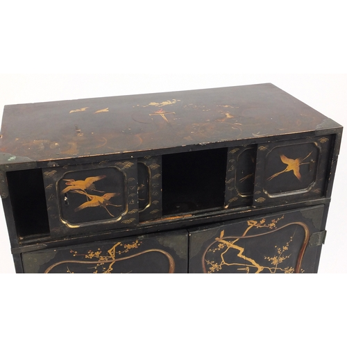 2014 - Black lacquered chinoiserie cabinet on stand, fitted with two pairs of sliding doors above a pair of...