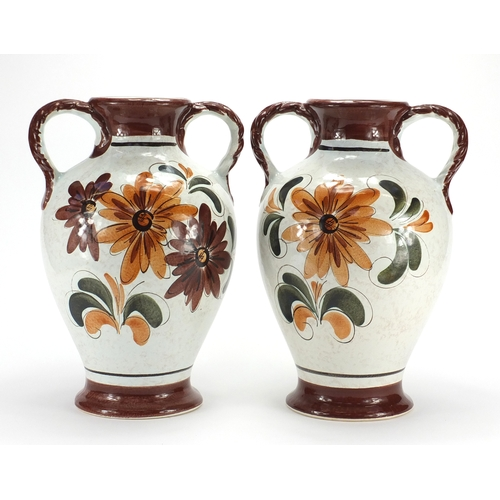 98 - Pair of Italian pottery twin handled vases, hand painted with flowers, 40cm high...