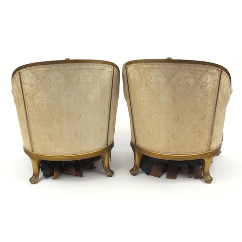 24 - Pair of French gilt wood tub chairs, with scroll arms, shell carved knees and floral upholstery, 81c...