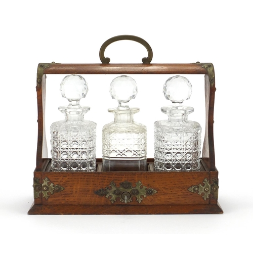 2044 - Edwardian oak tantalus with brass mounts and three cut glass decanters, 34cm H x 37cm W x 14.5cm D...