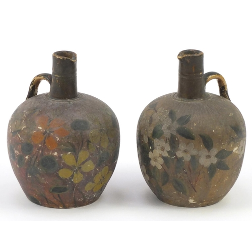 208 - Two Glasgow pottery jugs, hand painted with flowers, 20cm high...