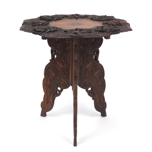 2018 - Anglo-Indian table on folding tripod base, profusely carved with fruiting vines, 61cm high x 63cm in...