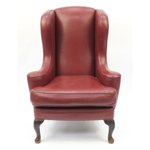 2016 - Burgundy leather wingback armchair raised on cabriole feet, 116cm high...