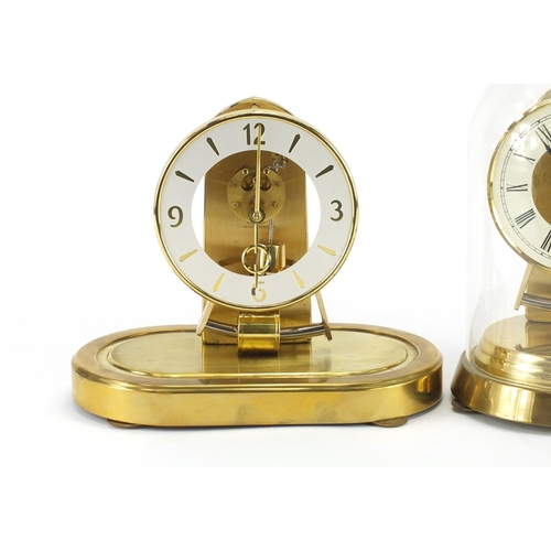 2112 - Two Kundo clocks including an Anniversary example under glass dome with Roman numerals, the largest ...