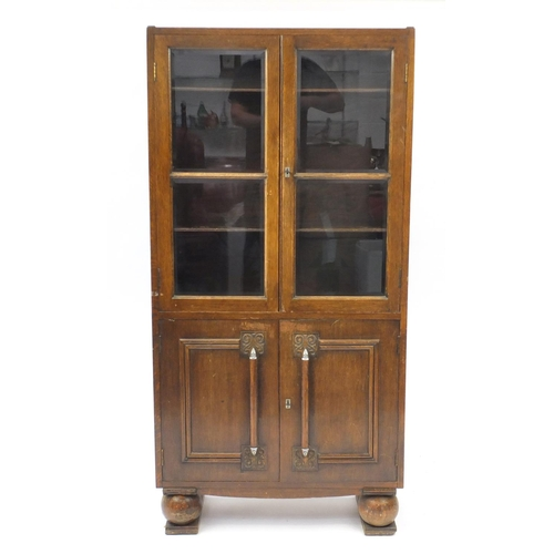 22 - Art Deco oak bookcase fitted with a pair of glazed doors above a pair of cupboard doors, 152cm H x 7...