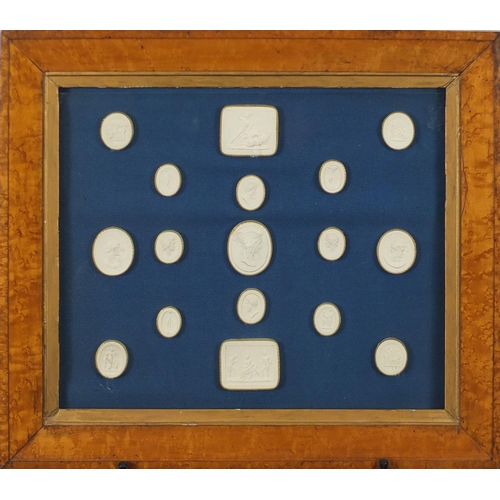 55 - Seventeen Grand Tour plaster cameos, mounted and housed in a birds eye maple frame, the largest came...