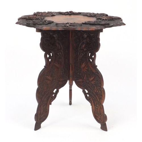 10A - Anglo-Indian table on folding tripod base, profusely carved with fruiting vines, 61cm high x 63cm in...