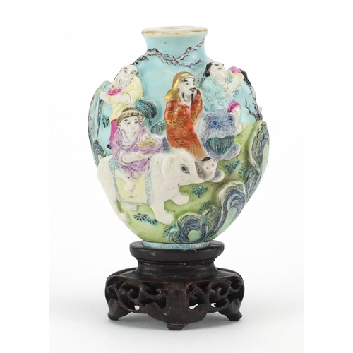 417 - Chinese porcelain relief snuff bottle raised on a carved hardwood stand, hand painted in the famille...