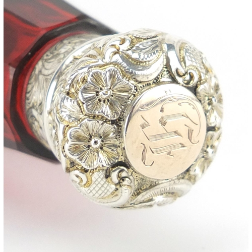 56 - Victorian ruby glass binocular double ended scent bottle having embossed unmarked silver mounts, 14c...