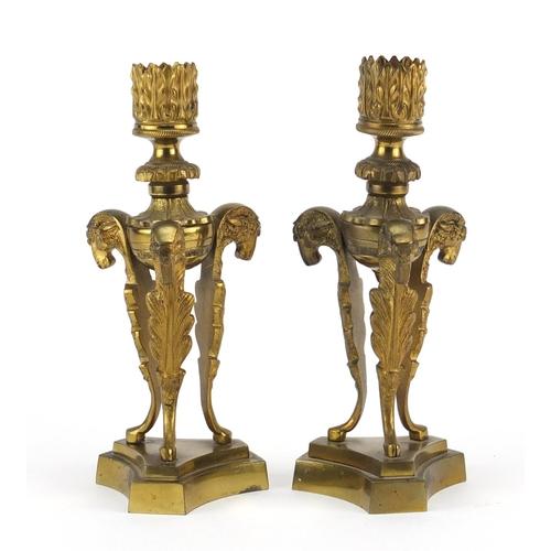 13 - Pair of 19th century gilt bronze ram design candlesticks raised on triangular bases, 18cm high...