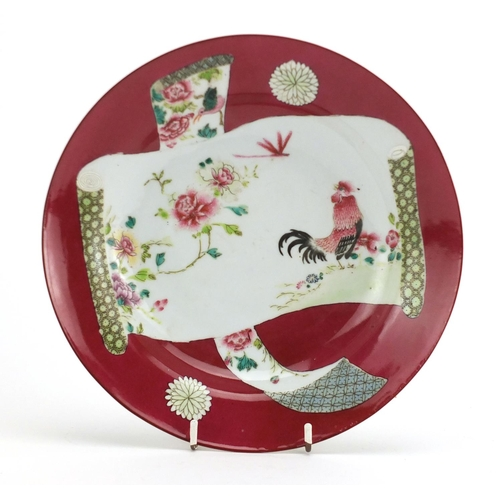 387 - Chinese porcelain red ground shallow dish, hand painted in the famille rose palette with a cockerel,...
