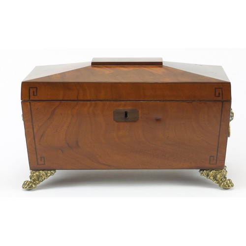 34 - Georgian inlaid mahogany sarcophagus shaped tea caddy, with ring turned lion head handles and paw fe...
