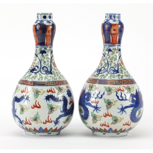 391 - Pair of Chinese porcelain doucai bottle vases, hand painted with flower heads and foliate scrolls am...
