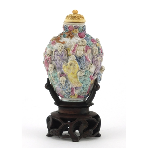 395 - Good Chinese porcelain relief snuff bottle with ivory stopper, raised on a carved hardwood stand, ha...