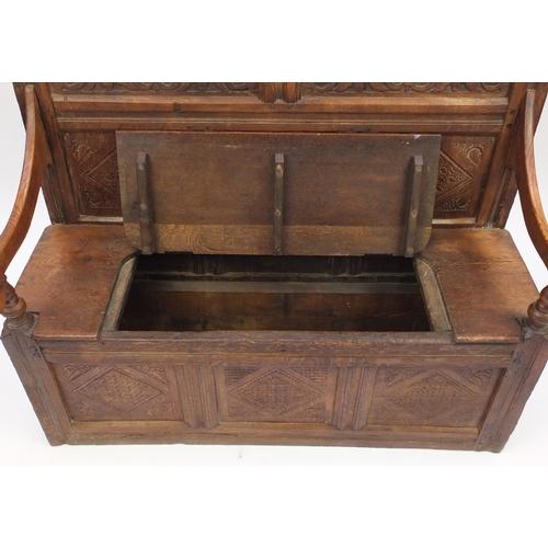 2028 - Antique carved oak three panel settle with lift up seat, 112cm H x 132cm W x 56cm D...