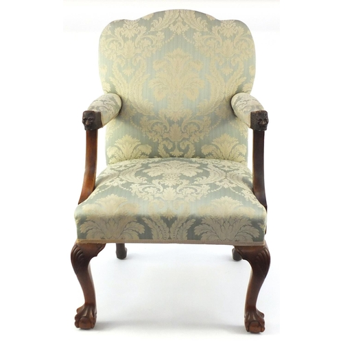 2007 - Walnut framed elbow chair carved with lion mask handles and having blue floral upholstery, 97cm high...
