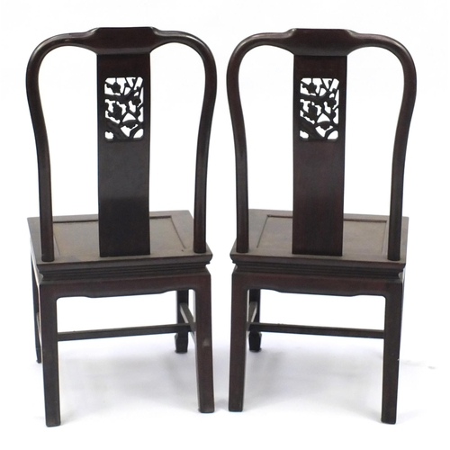 12 - Pair of Chinese hardwood chairs, the backs carved with a bird amongst flowers, 97cm high...