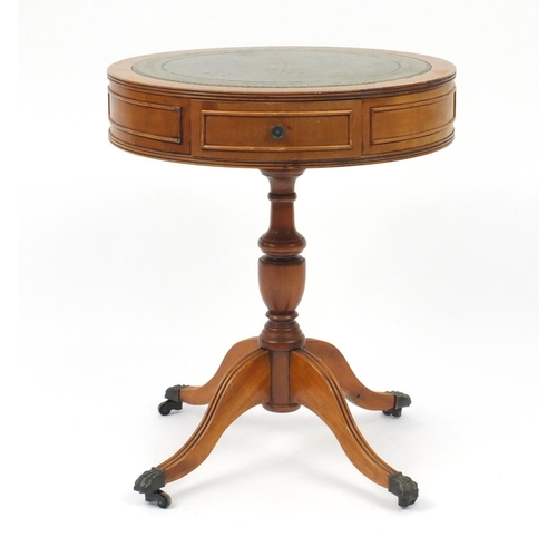 16 - Yew drum table with tooled leather insert and brass paw feet, 58.5cm high x 48.5cm in diameter...