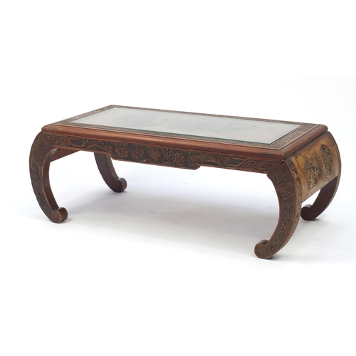 19 - Chinese hardwood coffee table with glass top, carved with figures in an interior, 36cm H x 97cm W x ...