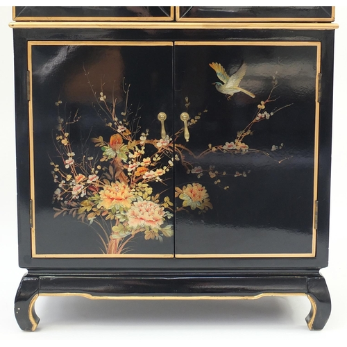 2004 - Chinese black lacquered display cabinet, hand painted with birds and flowers, having a pair of bevel...