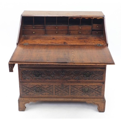 6 - Oak bureau profusely carved with floral motifs, the fall enclosing a fitted interior above four grad...