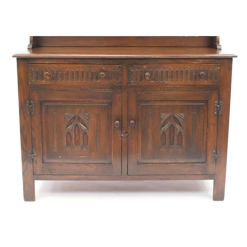 42 - Carved oak dresser with open plate rack above two drawers and a pair of cupboard doors, 167cmH x 128...