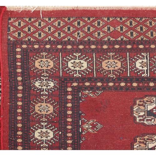 26 - Bokara red ground carpet runner with blue and cream motifs, 237cm x 79cm...