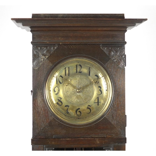 7 - Arts & Crafts carved oak eight day long case clock striking on a gong, the brass face with Arabic nu...