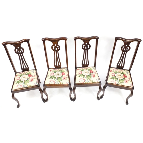 21 - Set of four stained beech chairs with pierced stylised backs, 102cm high...