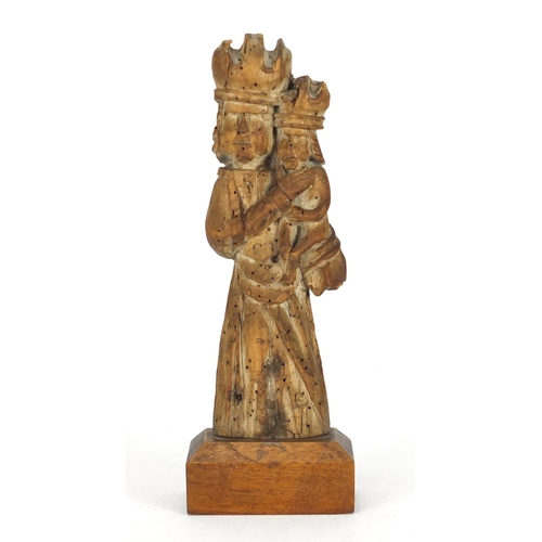 11 - 14th/15th century limewood carving of Madonna and child, raised on a rectangular mahogany block base...