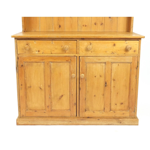 23 - Pine dresser with open plate rack above two drawers and a pair of cupboard doors, 198cm H x 122cm W ...