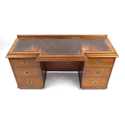 44 - Oak twin pedestal desk, the breakfront top with tooled leather insert, the six drawers with inset br...