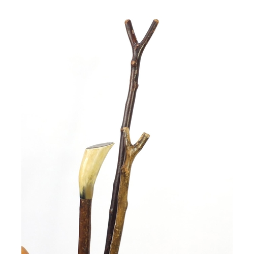 13 - Group of walking sticks and Military swagger sticks, some with horn handles, in a brass coal scuttle...