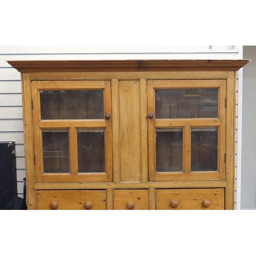 14 - Victorian pine side cabinet with a pair of glazed doors above three drawers and a pair of cupboard d...