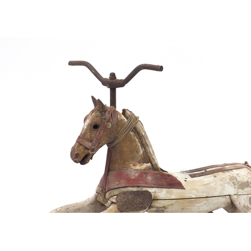 177 - Antique French carved wooden cast iron ride on pedal horse, 72cm in length...