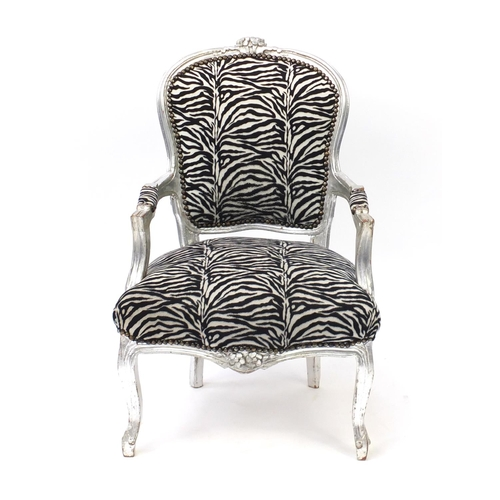 33 - Ornate silvered open armchair with zebra pattern upholstery, 92cm high...