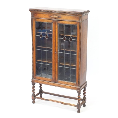 44 - Oak Arts & Crafts style bookcase, with leaded glass doors and three adjustable shelves, 141cm H x 80...