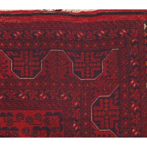 2033 - Rectangular Afghan red ground carpet, 202cm x 152cm...