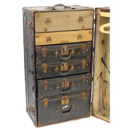 14 - Large vintage metal and leather bound steamer trunk, fitted with four suitcases, two drawers and war...