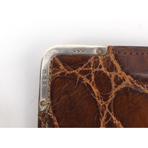 56 - Four crocodile skin effect leather wallets and purses, one with 9ct gold mounts the others with silv...