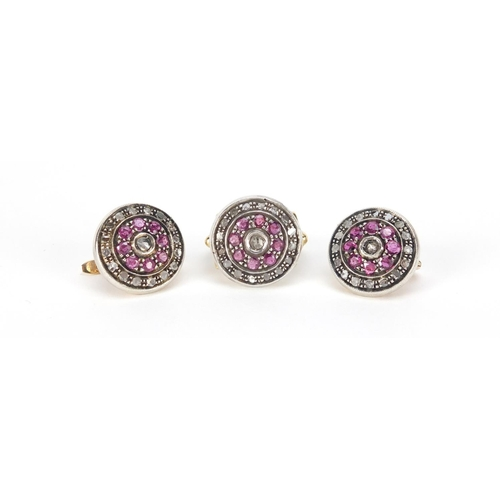 964 - 18ct gold ruby and diamond halo ring and a pair of matching earrings marked 500, the ring size N, 20...
