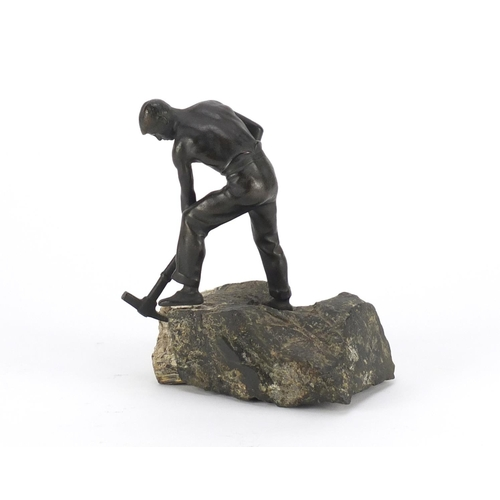 9 - Johann Robert Korn, patinated bronze of a young man with a pick axe, raised on a  naturalistic slate...
